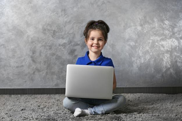 灰色の壁に毛皮のカーペットの上にラップトップを持つ少女