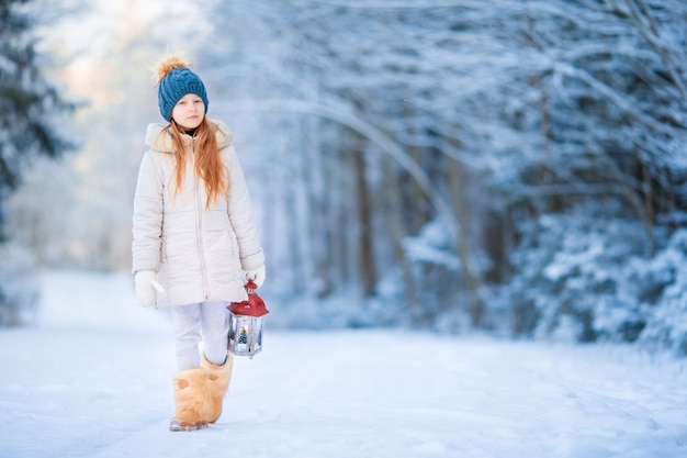 Little girl with latern in frozen forest on christmas eve