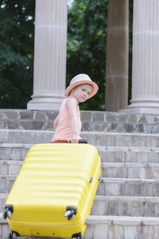 A little girl with light waves understands the steps of a large yellow suitcase. a beautiful child in a straw hat.