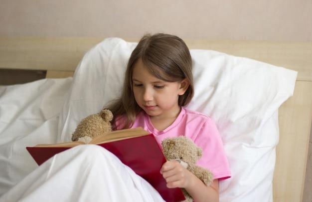 ピンクのtシャツを着た長いブロンドの髪の少女は、昼間はベッドに座って、テディベアに本を読みます