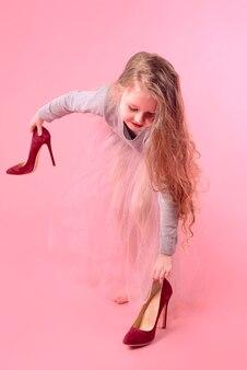 분홍색 치마에 긴 금발 머리를 가진 어린 소녀와 엄마 빨간 하이힐 신발 성인 연주