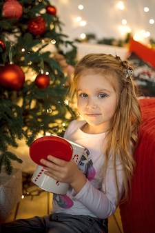 A little girl with long blonde hair opened a christmas gift