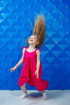 Маленькая девочка с длинными вьющимися волосами в розовом платье на синем фоне танцует и смеется, яркие детские эмоции радости, счастливое детство