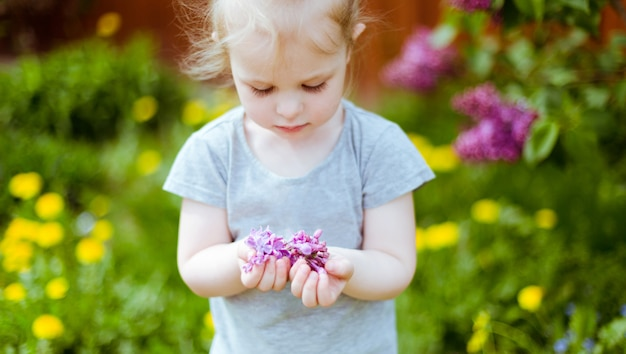 A little girl with long dark eyelashes gently holding a handful of lilac flowers. selective focus