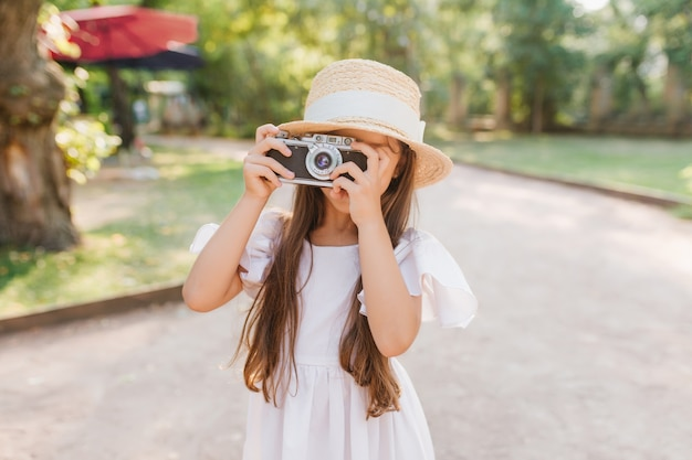 Little girl with long dark hair holding camera in hands standing on the alley in park. female child in straw hat with white ribbon taking photo of nature view in sunny day.