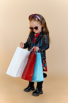 スタイリッシュな秋の服とサングラスで長い髪の少女