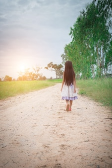 Little girl with long hair wearing dress is walking away from yo