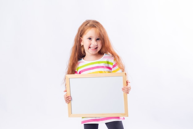 Little girl with long red hair is smiling and holding a white drawing board