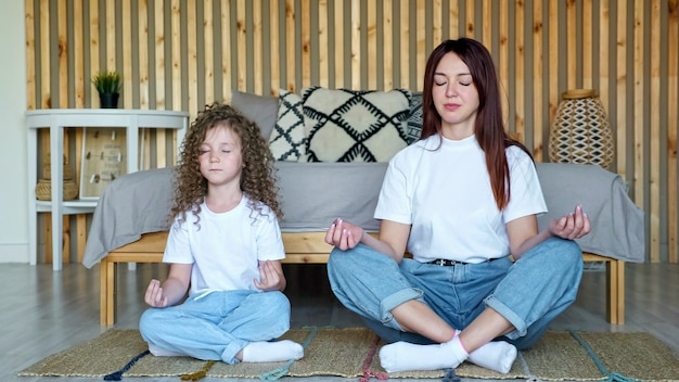 Маленькая девочка с распущенными волосами и мама сидят в позах йоги