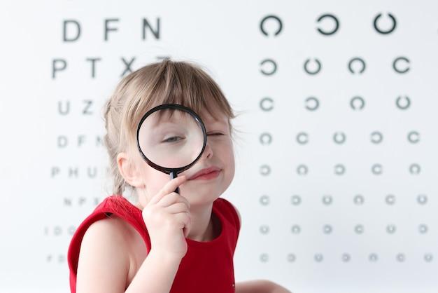 시력 검사를 위해 테이블의 벽에 돋보기 서있는 어린 소녀