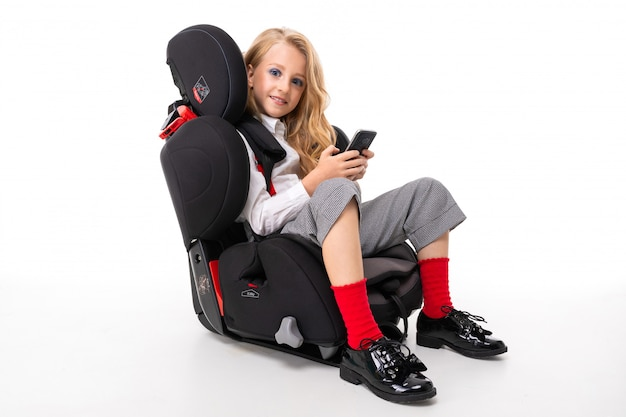 A little girl with makeup and long blonde hair sitting in a car baby chair with mobile phone