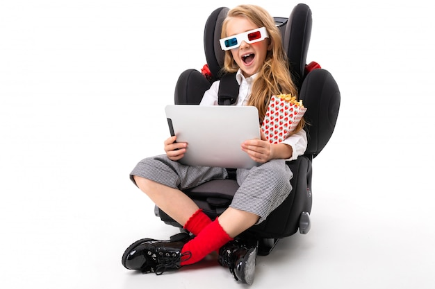 A little girl with makeup and long blonde hair sitting in a car baby chair with tablet, earphones, pop-corn, 3d glasses and watch interesting film of cartoon