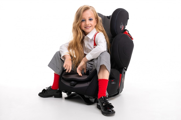 A little girl with makeup and long blonde hair sitting in a car baby chair