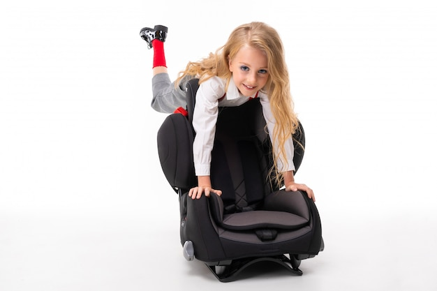A little girl with makeup and long blonde hair with a car baby chair