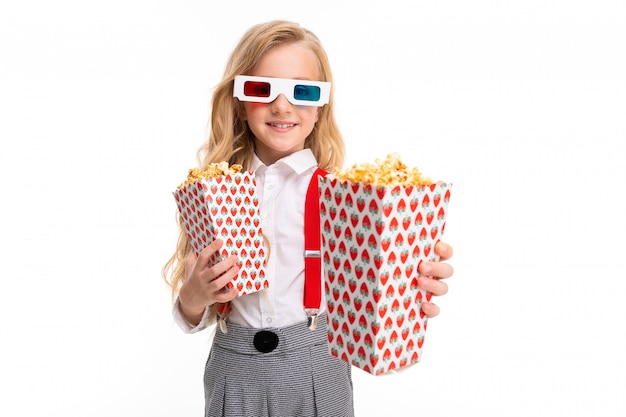 A little girl with makeup and long blonde hair with pop-corn and 3d glasses and smiles
