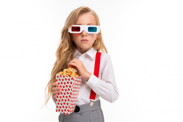 A little girl with makeup and long blonde hair with pop-corn and 3d glasses