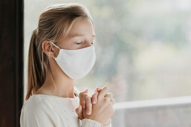 Bambina con la mascherina medica che prega