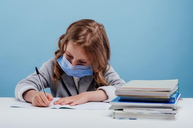 의료 마스크를 쓴 어린 소녀는 파란색 배경에 격리된 테이블에 앉아 있는 공책에 글을 씁니다.