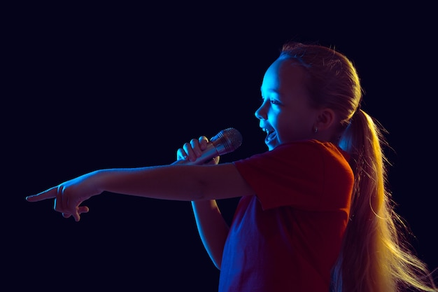 Little girl with microphone in neon light