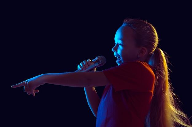 Bambina con microfono in luce al neon