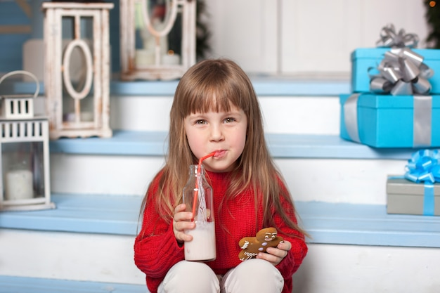 Little girl with milk and a gingerbread man sitting on porch near house. child eats cookies with milk on porch at home. toddler with a glass of milk and christmas candy. child with christmas present.