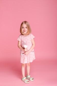 분홍색 표면에 우유와 어린 소녀