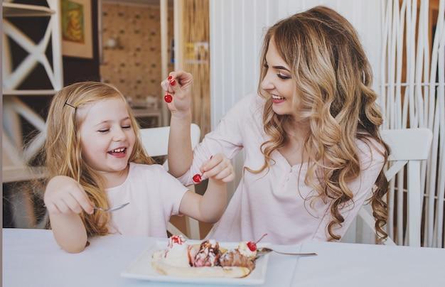 Маленькая девочка с мамой и кормят друг друга вишневым мороженым в уютном кафе. хорошие отношения родителей и ребенка.