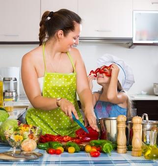 キッチンでお母さんのある小さな女の子