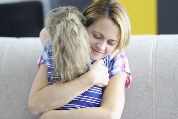 Маленькая девочка с мамой, обнимая на диване у себя дома.