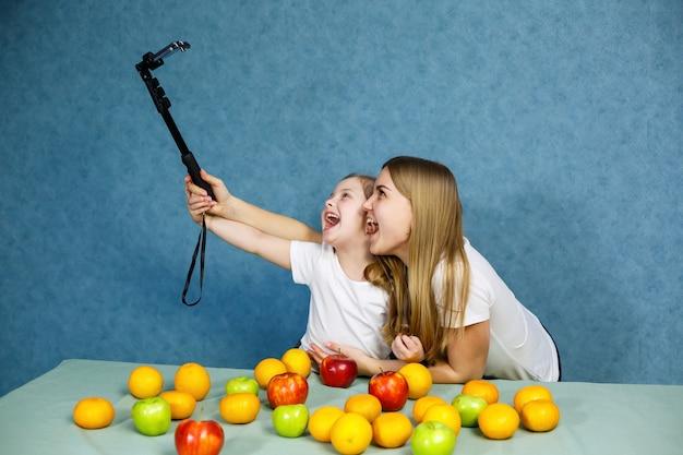白いtシャツを着たお母さんと一緒に小さな女の子が電話で自分撮りをして遊ぶ