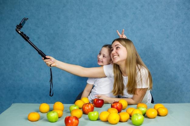 Маленькая девочка с мамой в белых футболках делает селфи по телефону и играет