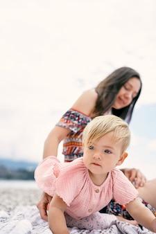 Маленькая девочка с мамой сидит на одеяле на пляже
