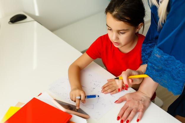 Маленькая девочка с мамой учится