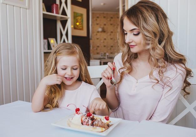 Маленькая девочка с матерью ест мороженое в уютном кафе. хорошие отношения родителей и ребенка.