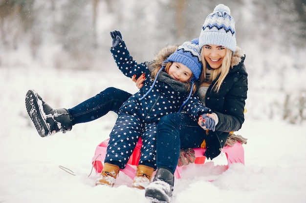 Little girl with mother playing in a winter park