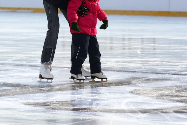 Little girl with mother skate on the rink