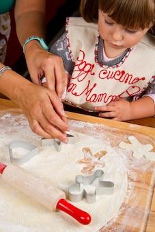 クッキーカッターでペストリーを切るクリスマスクッキーを焼くお母さんと小さな女の子