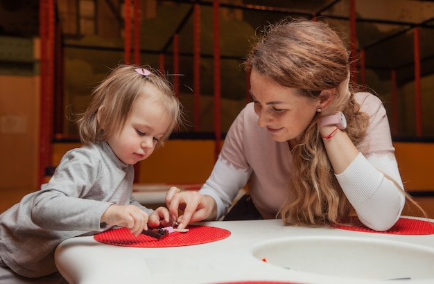 Little girl with a nanny plays toy bricks at table in a children's entertainment center