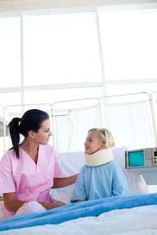 Little girl with a neck brace smiling at the nurse