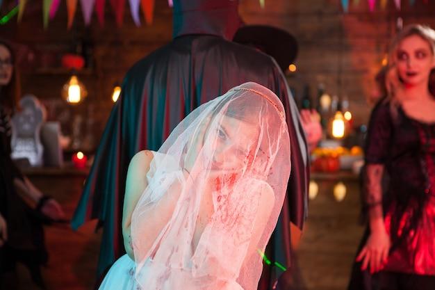 Маленькая девочка без эмоций, одетая как невеста на хэллоуин. празднование хэллоуина. человек в костюме дракулы размывается на заднем плане.