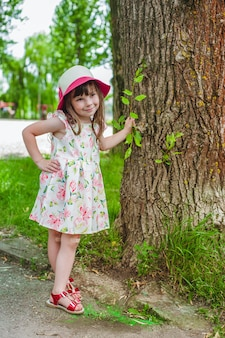 Little girl with one hand leaning on a tree