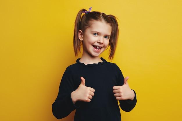 Маленькая девочка с открытым ртом показывает палец вверх изолирована на желтой стене