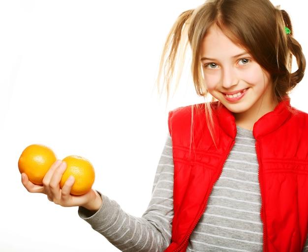 Маленькая девочка с апельсинами и соком. изолированные на белом.