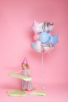 모자에 종이와 분홍색 표면에 풍선 어린 소녀
