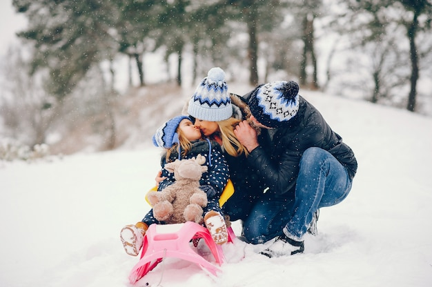 Little girl with parents playing in a winter park