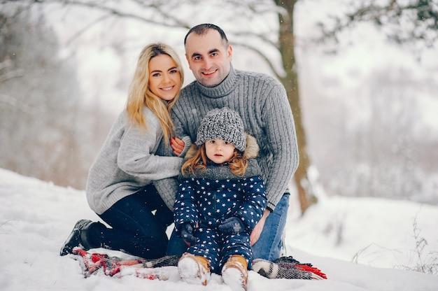 Маленькая девочка с родителями сидит на одеяле в зимнем парке