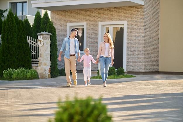 새 건물 근처를 걷는 부모와 어린 소녀