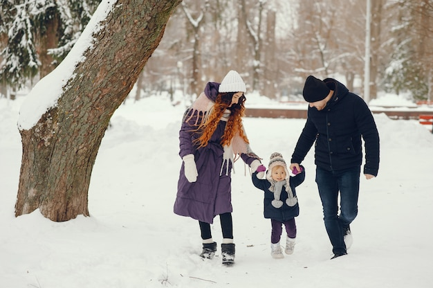 Little girl with parents in a winter park