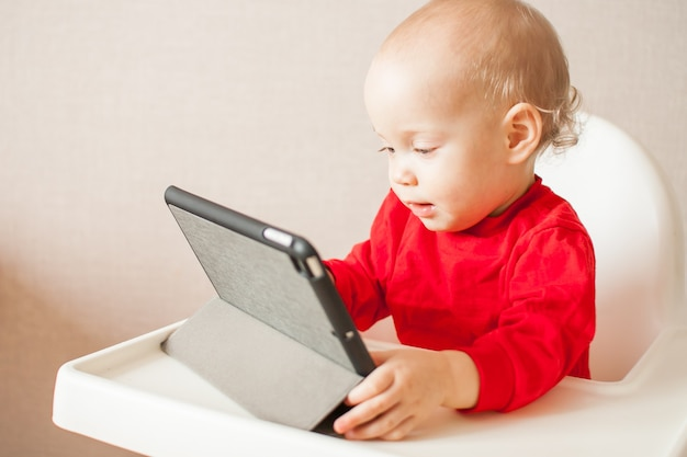 열정을 가진 어린 소녀가 태블릿에서 온라인 교육 프로그램을보고 있습니다.