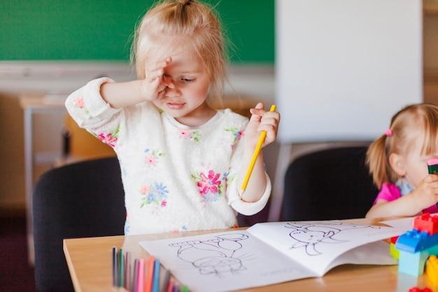 Маленькая девочка с книгой для рисования карандашом